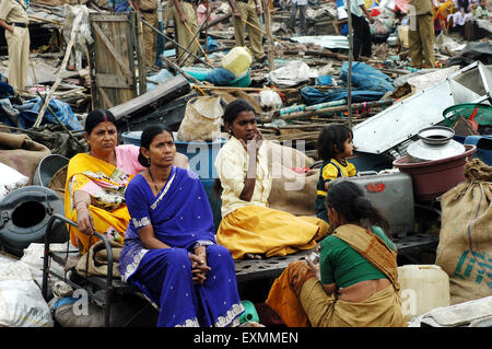 Slum dwellers sit with their belongings after the demolition of illegal slums on the Mankhurd Link Road Mumbai