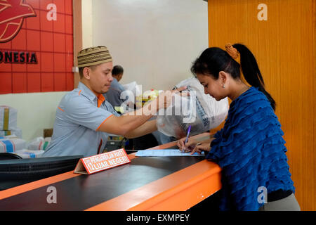 female customer signing for a delivery at the main post office in malang java indonesia - Stock Photo