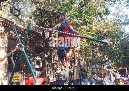 Woman balance rope kala ghoda fair Bombay Mumbai Maharashtra India - Stock Photo