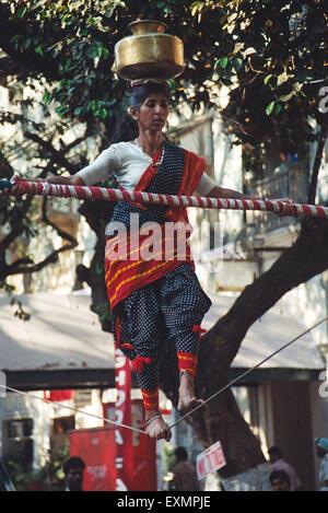 Woman balance rope pot kala ghoda fair Bombay Mumbai Maharashtra India - Stock Photo