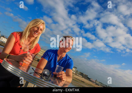 A young couple enjoying a drink along the harbour arm at Margate. Kent. UK - Stock Photo