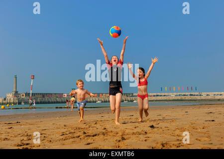 Children with a beach ball on Margate beach. Kent. UK - Stock Photo