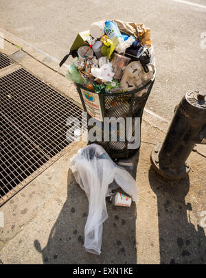 An overflowing trash can in the Chelsea neighborhood of New York on Saturday, July 11, 2015. (© Richard B. Levine) - Stock Photo