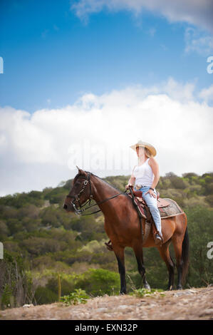 USA, Texas Hill Country, cowgirl sitting on horse - Stock Photo