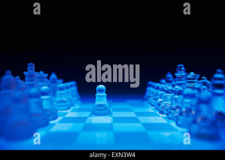 Chess pieces on blue glass board against dark background - Stock Photo