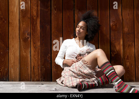 Sunbathing young woman leaning on wooden wall - Stock Photo