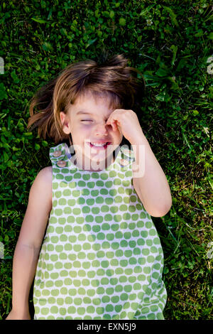 Smiling little girl with closed eyes lying on a meadow - Stock Photo