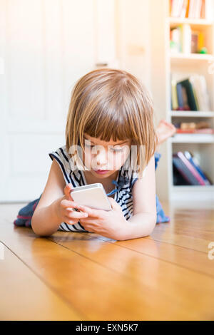 Little girl lying on wooden floor with smartphone - Stock Photo