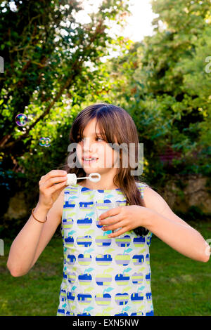 Girl blowing soap bubbles in a garden - Stock Photo