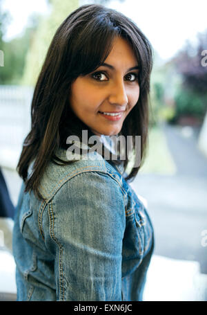 Portrait of smiling woman wearing jeans jacket - Stock Photo