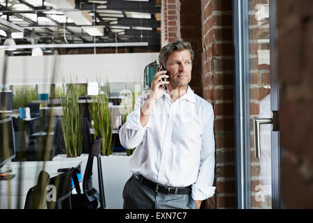 Businessman in office on smartphone looking out of window - Stock Photo