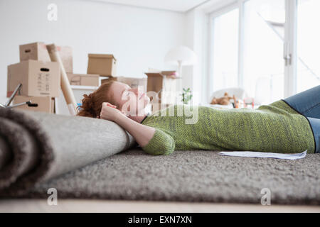 Young woman in new flat with cardboard boxes lying on carpet - Stock Photo