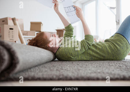 Young woman in new flat with cardboard boxes looking at ground plan - Stock Photo