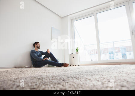 Young man sitting on the floor of living room looking through window - Stock Photo