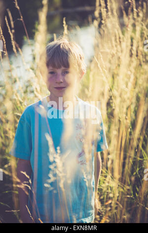 Little boy standing on a meadow at backlight - Stock Photo