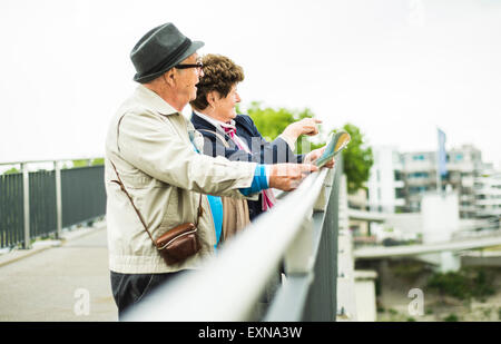 Senior couple with map standing on a bridge looking at view - Stock Photo