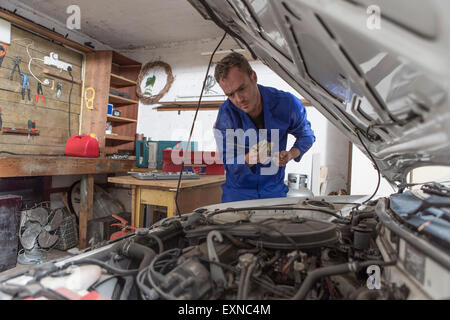 Man working on car in home garage looking at dipstick - Stock Photo
