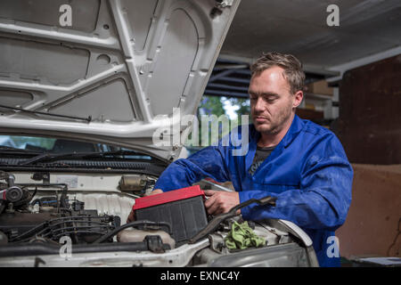 Man working on car in home garage removing battery - Stock Photo