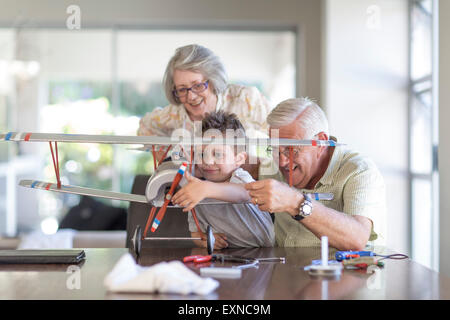 Grandfather and grandson building up a model airplane watched by grandmother - Stock Photo