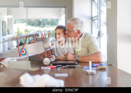Grandfather and grandson building up a model airplane - Stock Photo