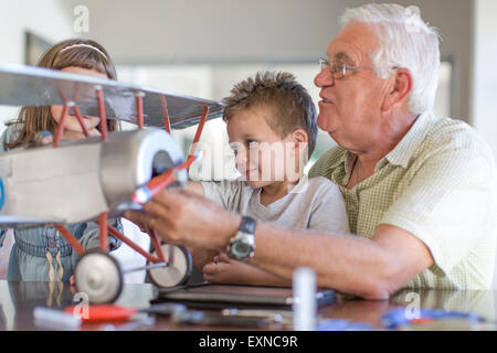 Grandfather and grandchildren building up a model airplane - Stock Photo
