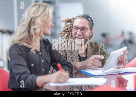 Portrait of a man showing his colleague something on mini tablet - Stock Photo