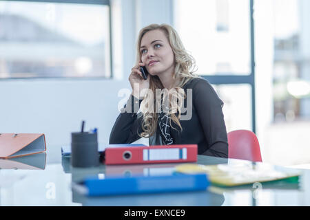 Portrait of blond woman telephoning with smartphone in an office - Stock Photo