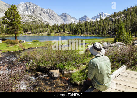 Resting hiker admires view in Little Lakes Valley in Rock Creek Canyon in the Eastern Sierra in Northern California - Stock Photo