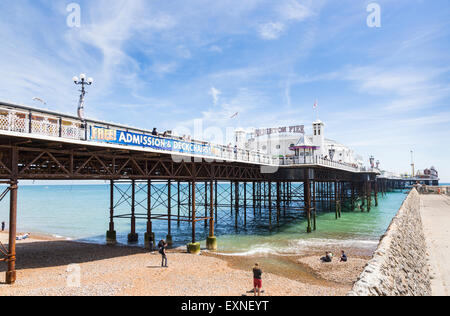 Victorian Palace Pier, or Brighton Pier, an iconic landmark, and beach on a hot, sunny summer day with blue sky, - Stock Photo