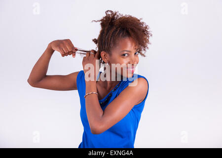 Young African American woman making braids to her frizzy afro hair - Black people - Stock Photo