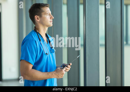 thoughtful male doctor holding tablet computer - Stock Photo