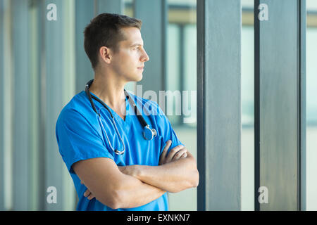 thoughtful doctor looking through office window - Stock Photo