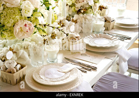 Image of a unique white wedding banquet table with place settings - Stock Photo