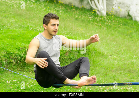 Man sitting on slackline left arm to the side concentrating keeping balance with grassy background - Stock Photo