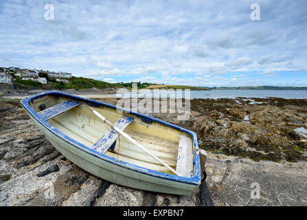 A dinghy on the beach at Portscatho a small picturesque fishing village near St Mawes on the Cornish coast - Stock Photo