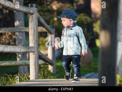 Young child walking across a wooden bridge. - Stock Photo