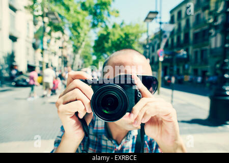 a young caucasian man wearing sunglasses points his camera to the observer at La Rambla in Barcelona, Spain - Stock Photo