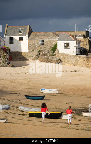 St Ives, Cornwall, UK: Two teenage girls running along St Ives Harbour beach in the late afternoon sun. - Stock Photo