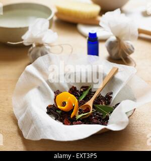 Dried rosehip, hibiscus, cloves, juniper berries, bay leaves, orange peel in bowl lined with muslin, tied-up muslin - Stock Photo