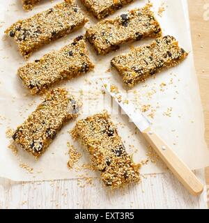 Home-made muesli bars on baking paper, with a knife - Stock Photo