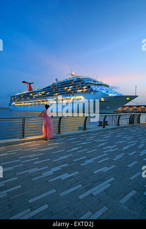 Woman admiring cruise ship from  Bahia Urbana (Urban Bay), Old San Juan, Puerto Rico - Stock Photo