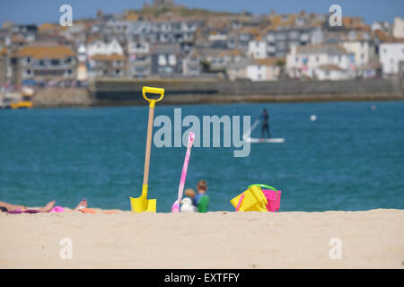 St Ives, Cornwall, UK:  Buckets and Spades on Portminster Beach with St Ives town in the background. - Stock Photo