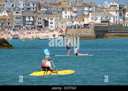 St Ives, Cornwall, UK:  man on Kayak and couple on paddle-board enjoy the water with St Ives in background. - Stock Photo