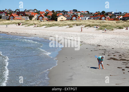 Surf at Hundested Beach on a summer's day. Boy drawing in the sand with a stick. - Stock Photo