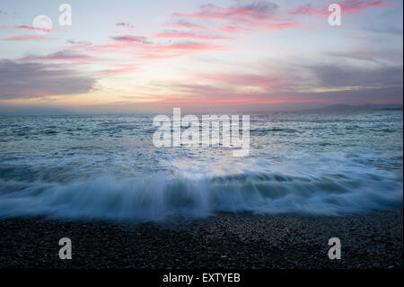 Ocean landscape with waves breaking on beach and moon clouds. - Stock Photo