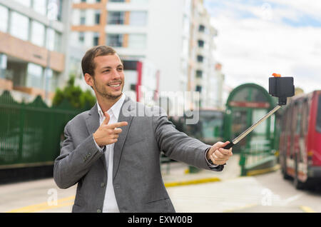 Man wearing formal clothing posing with selfie stick in urban environment smiling making gun of right hand plus - Stock Photo