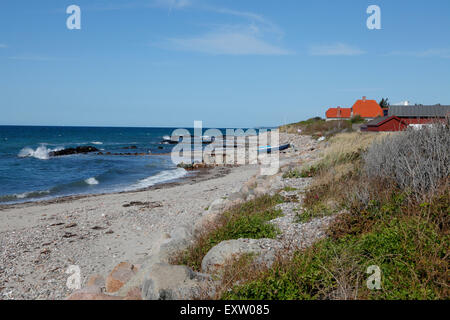 Viewing east along the rough coast of the fishing hamlet Kikhavn near Hundested on a sunny summer's day. - Stock Photo
