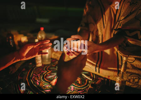 A man receives a cup of Ayahuasca, a traditional Amazonian plant medicine used to induce hallucinogenic visions - Stock Photo