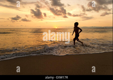 Boy silhouette running through water on the beach at sunset. - Stock Photo
