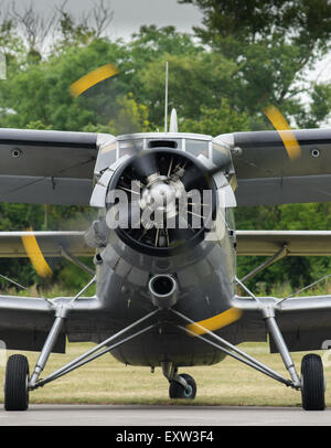 Front view of an old vintage biplane with rotating propeller, waiting on an airfield shortly before the start. - Stock Photo